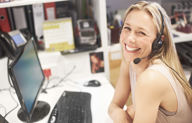 Allianz - A young woman smiling while sitting at a computer on a desk.